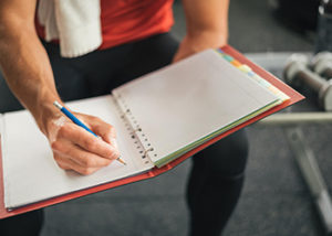 person writing in a journal to track fitness progress