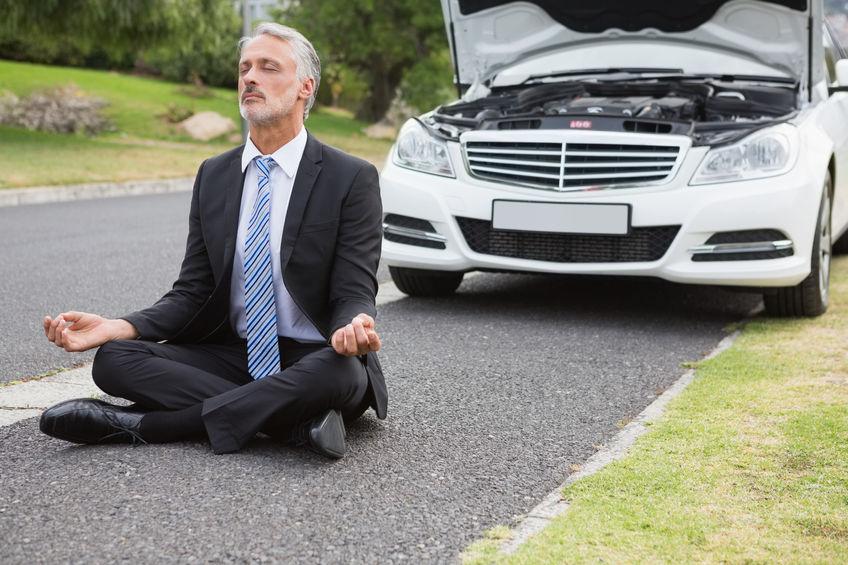 man meditating in front of broken down car