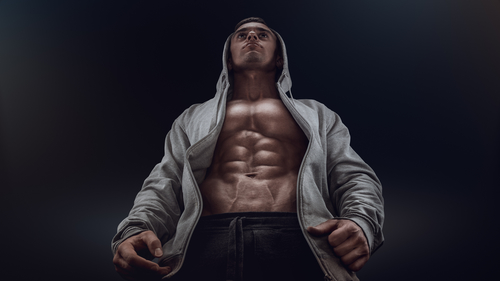 Bottom view of young strong bodybuilder showing off his physique against black background. Confident young fitness man with strong hands, abs and abdominal muscles best probiotic for men